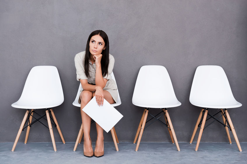43297081 - bored young businesswoman holding paper and looking away while sitting on chair against grey background