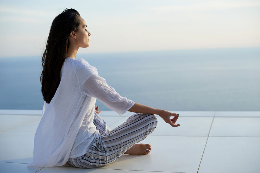 43315420 - young woman practice yoga meditaion on sunset with ocean view in background