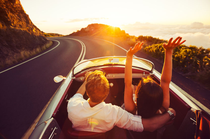 44181473 - happy couple driving on country road into the sunset in classic vintage sports car