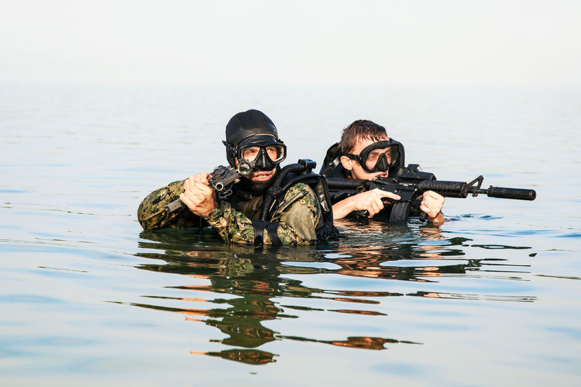 51068834 - navy seal frogmen with complete diving gear and weapons in the water