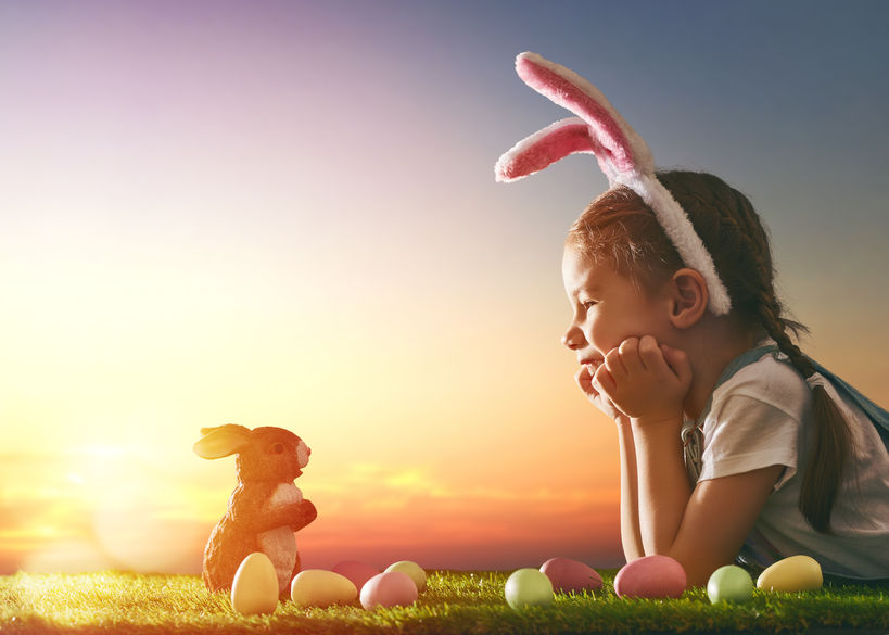 52154679 - cute little child girl wearing bunny ears on easter day. girl hunts for easter eggs on the lawn. girl with easter eggs and bunny in the rays of the setting sun.