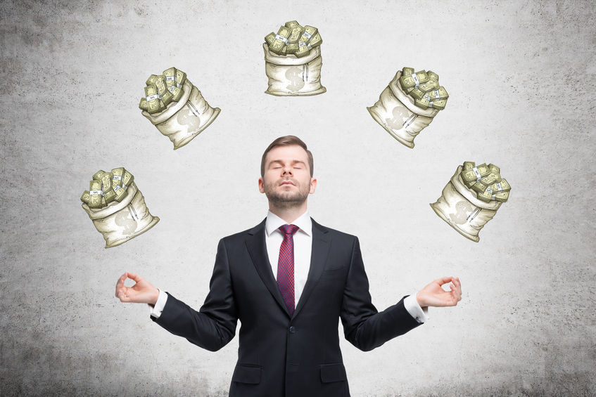 52395260 - a young businessman standing in the posture of meditation with eyes closed at a concrete wall with five sacks of dollars on it. front view. concept of dreaming about money.
