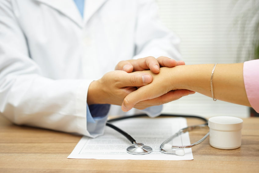 54519933 - doctor holding patient hand with compassion and comfort