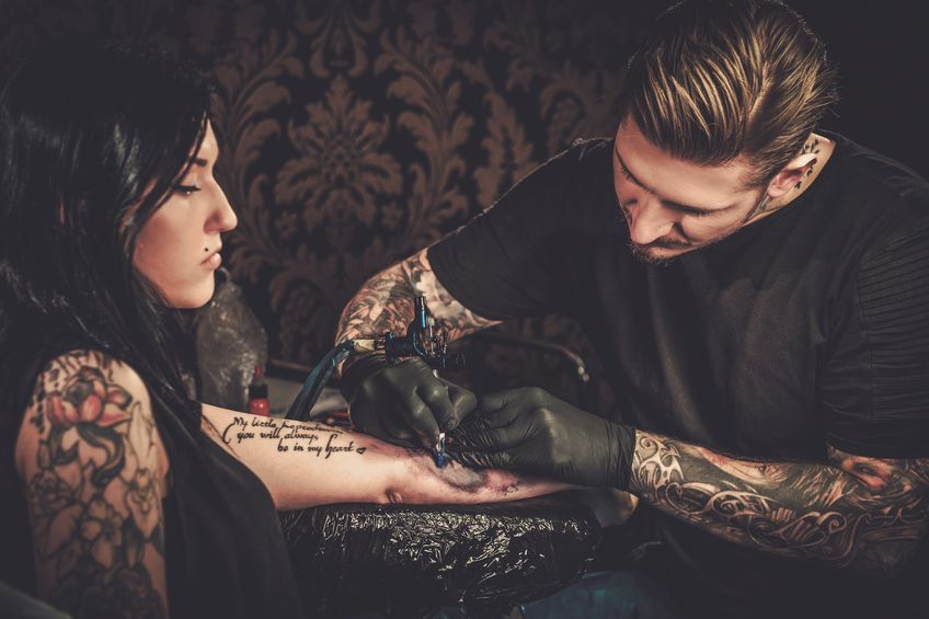 57069416 - professional tattoo artist makes a tattoo on a young girl's hand.
