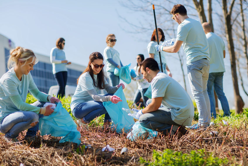 62353809 - volunteering, charity, cleaning, people and ecology concept - group of happy volunteers with garbage bags cleaning area in park