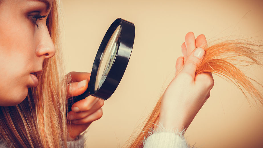 70121172 - haircare, health problem concept. unhappy blonde woman looking at ends of her blonde hair through magnifying glass