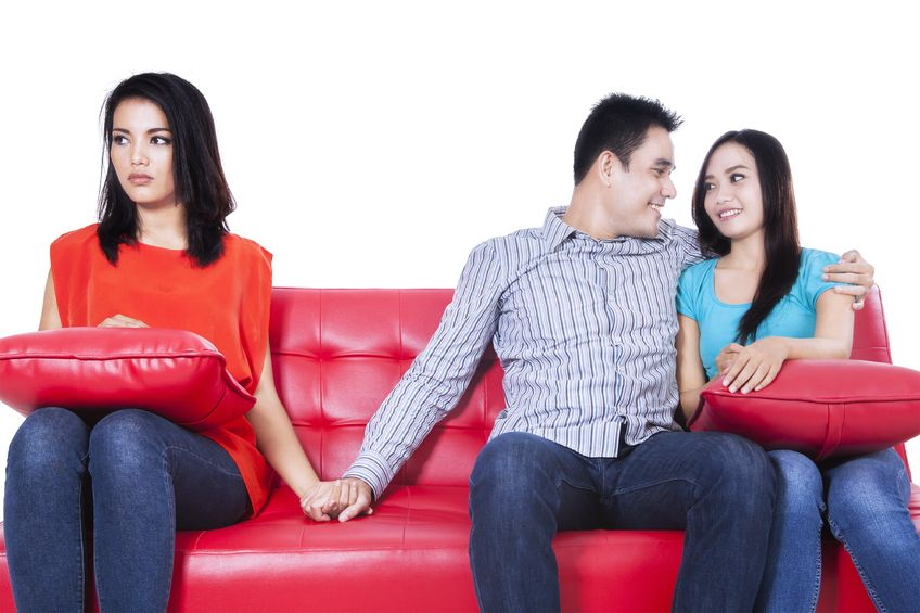 22114528 - beautiful young woman holding hands with man sitting near his girlfriend