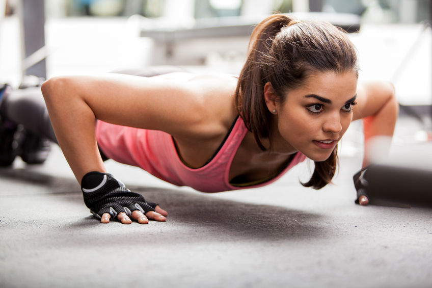 24382121 - beautiful latin woman doing push ups in the gym before lifting some weights