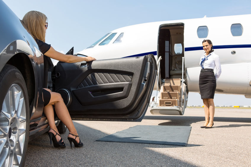 25768427 - elegant woman stepping out of car parked in front of private plane and airhostess