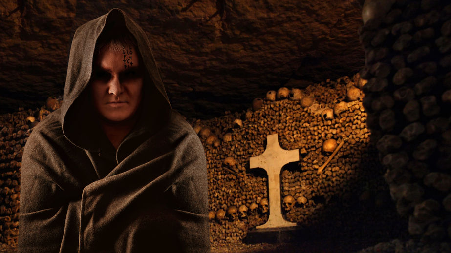 25997749 - praying monk in the dark paris catacombs