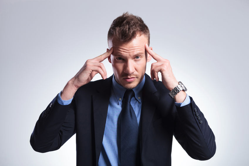 27837586 - young business man concentrating with his fingers at his temples while looking into the camera. on a light gray studio background