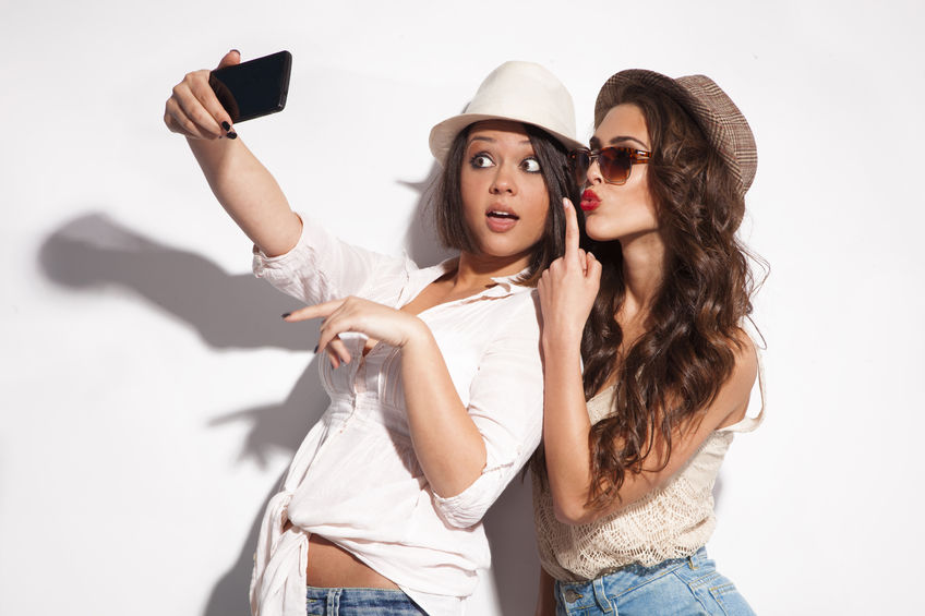28343887 - two young women taking selfie with mobile phone
