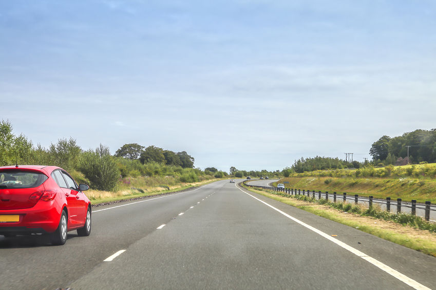 31428206 - red car driving on the left side of a quiet motorway