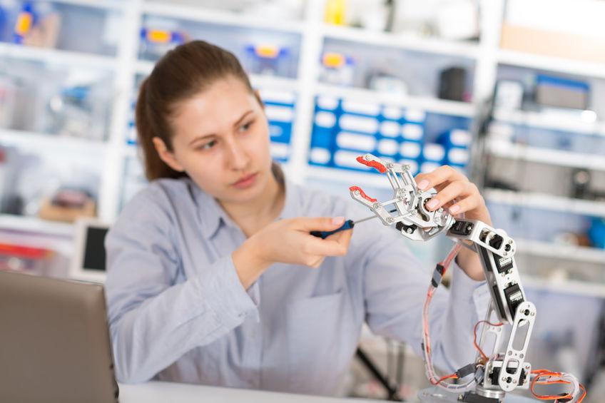 34147378 - schoolgirl adjusts the robot arm model, girl in a robotics laboratory