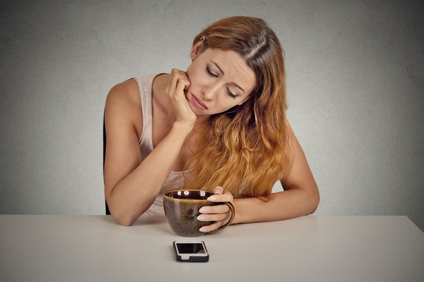 36468116 - sad depressed young woman sitting at table drinking coffee looking at her mobile phone waiting for a call text message isolated on grey wall background.