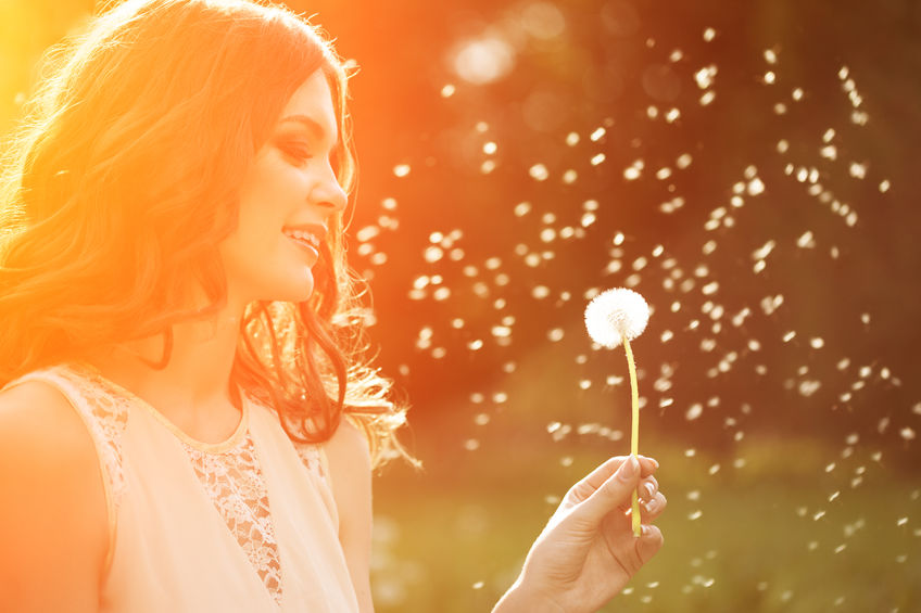 39394923 - young spring fashion woman blowing dandelion in spring garden. springtime. trendy girl at sunset in spring landscape background. allergic to pollen of flowers. spring allergy