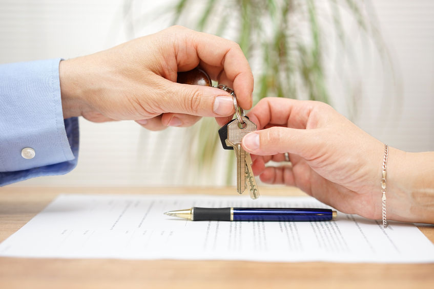 43131862 - real estate agent gives house keys to his client after signing contract