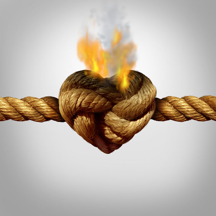 44492771 - divorce and separation concept as a rope with a burning knot shaped as a love heart as a relationship problem symbol or infidelity crisis icon between a couple.
