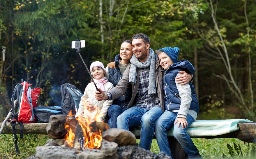 49276540 - camping, travel, tourism, hike and people concept - happy family sitting on bench and taking picture with smartphone on selfie stick at campfire in woods