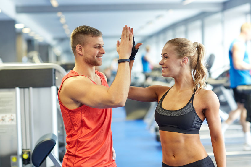 54750894 - sport, fitness, lifestyle, gesture and people concept - smiling man and woman doing high five in gym