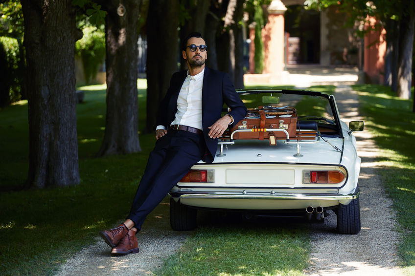 58050966 - successful and wealthy businessman enjoying a day during trip on luxury cabriolet car on countryside road, sure and confident handsome man with his new convertible car and villa house on background