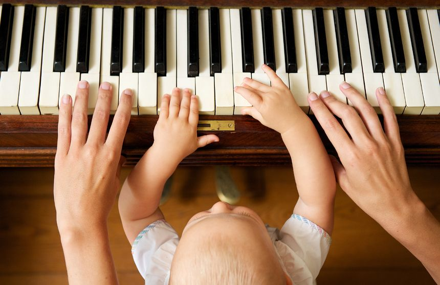 21144746 - closeup portrait of a baby learning to play piano with mother - from above