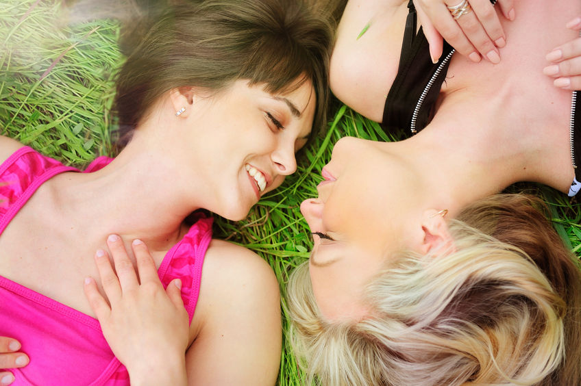 38211424 - outdoor portrait of a lesbian girlfriends couple laying in grass, smiling and looking each other.