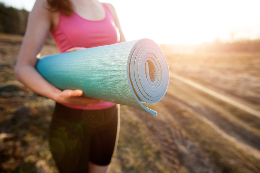 41230395 - woman walking with a yoga mat outside during sunset n a rural area wearing sports wear and doing yoga