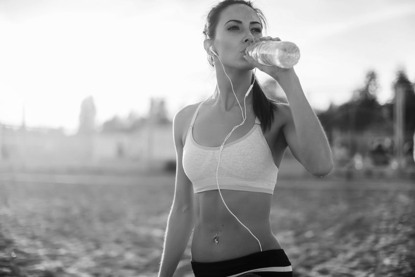 43880602 - beautiful fitness athlete woman resting drinking water after work out exercising on beach summer evening in sunny sunshine outdoor portrait.