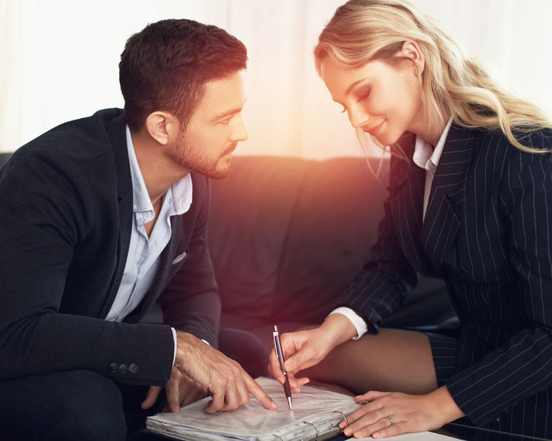 59809280 - young manager flirting with businesswoman in sunset, review contract, indoors