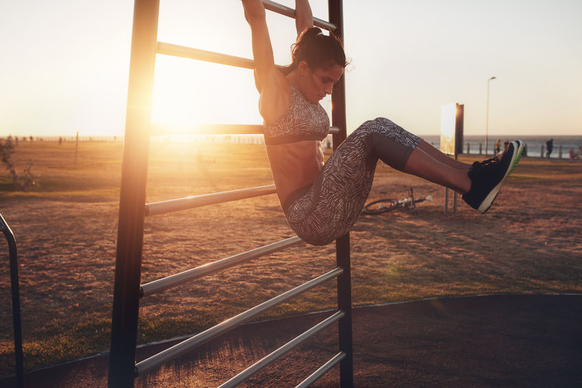 60508650 - candid shot of real healthy and fit woman performing hanging leg raises on outdoor fitness station in sunset at beach promenade. showing strong abdominal six-pack.