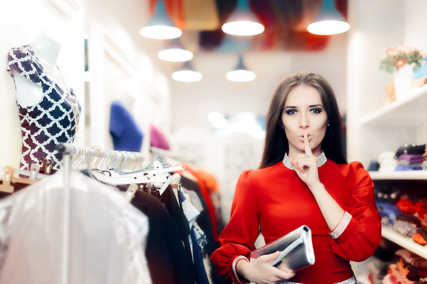 64861982 - elegant woman keeping a secret in fashion store