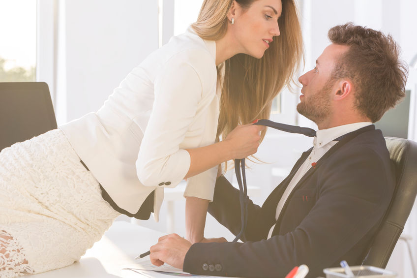 67284823 - shot of a beautiful woman sitting on a desk in an office and holding elegant man's tie