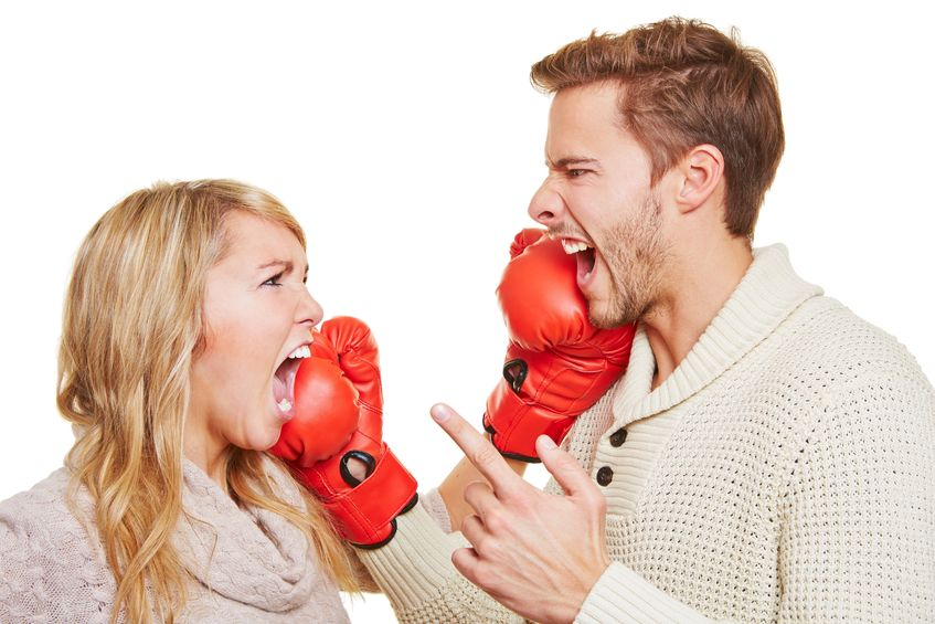 16979723 - screaming angry couple fighting with red boxing gloves