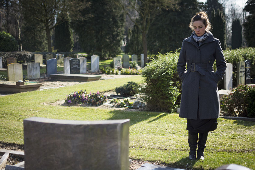 26559211 - widow standing at graveyard looking at grave