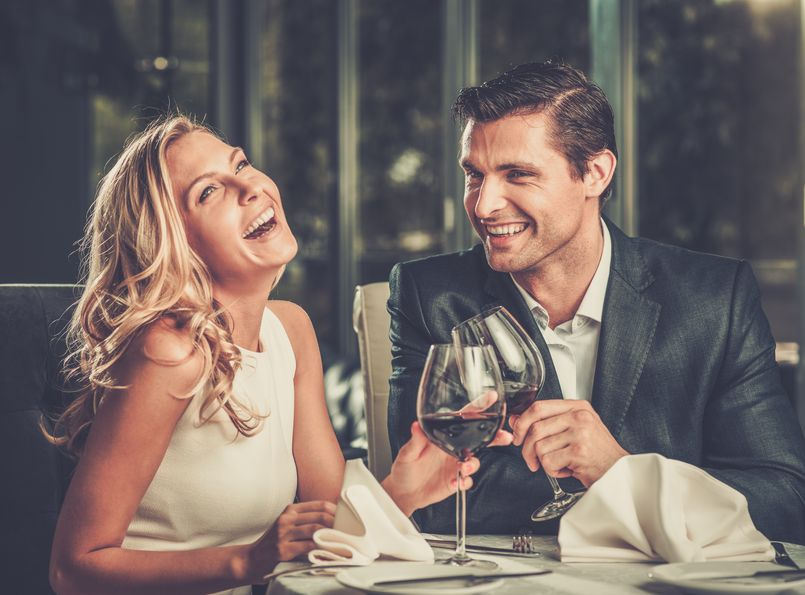 29540051 - cheerful couple in a restaurant with glasses of red wine