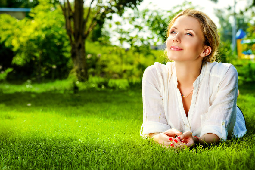 31798231 - beautiful smiling woman lying on a grass outdoor. she is absolutely happy.