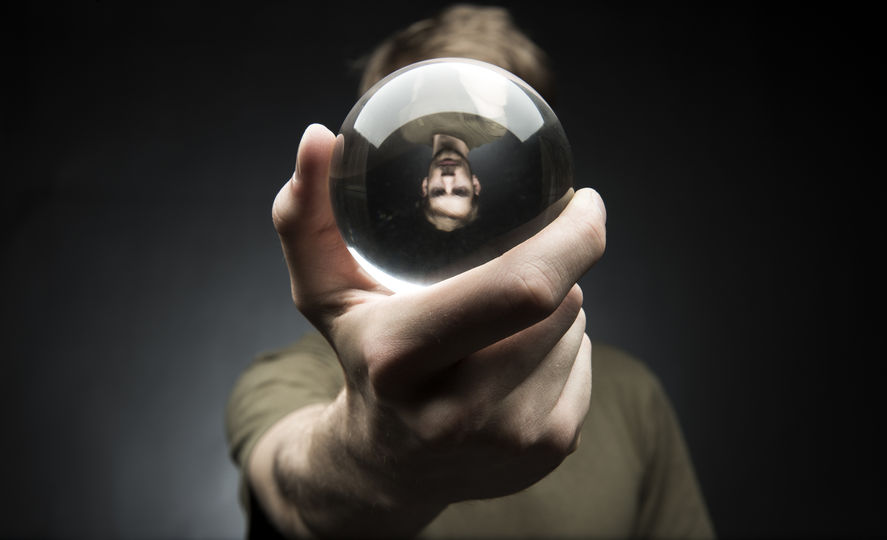 34556520 - young man holding a clear transparent crystal glass ball in their hand