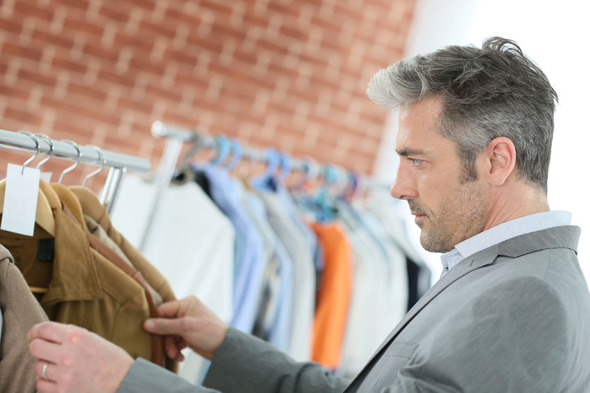 38397009 - mature man choosing clothes in shop