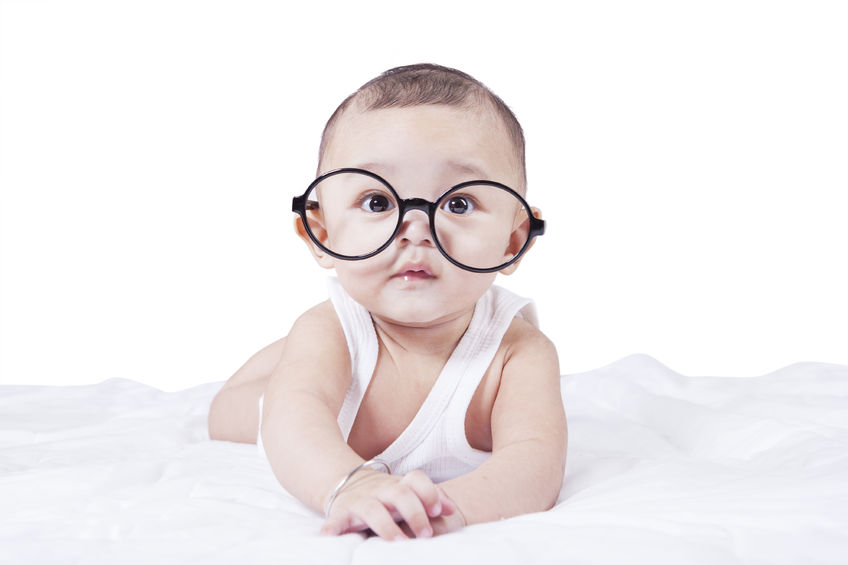 39887153 - portrait of little baby boy looking at the camera while lying on bed and wearing a round glasses