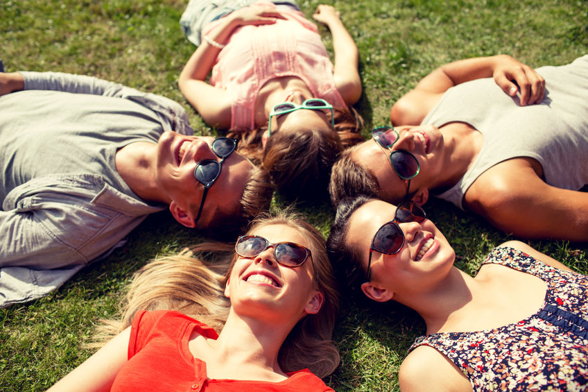 41729173 - friendship, leisure, summer and people concept - group of smiling friends lying on grass in circle outdoors