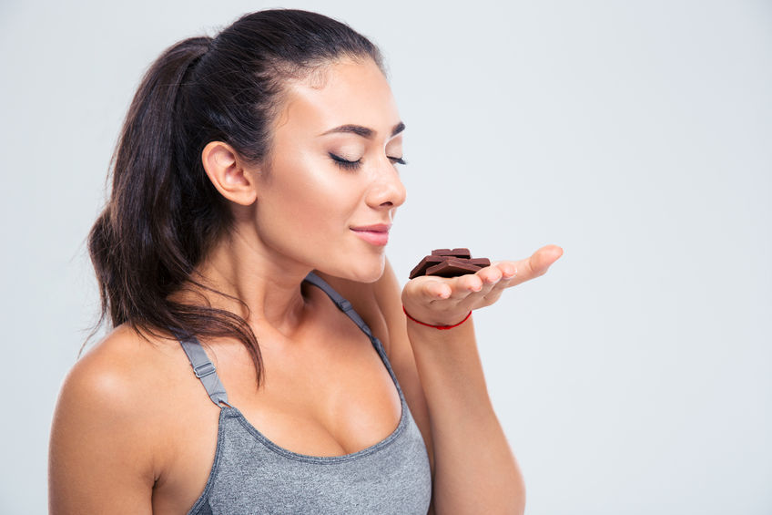 44276850 - portrait of a pretty girl smelling chocolate isolated on a white background