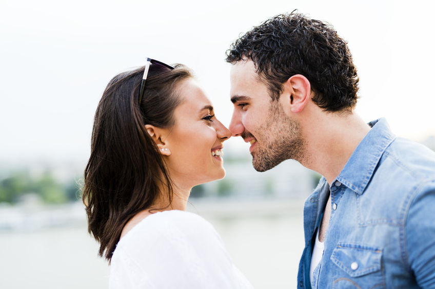 44976417 - young beautiful couple rubbing noses as a sign of love and about to kiss each other