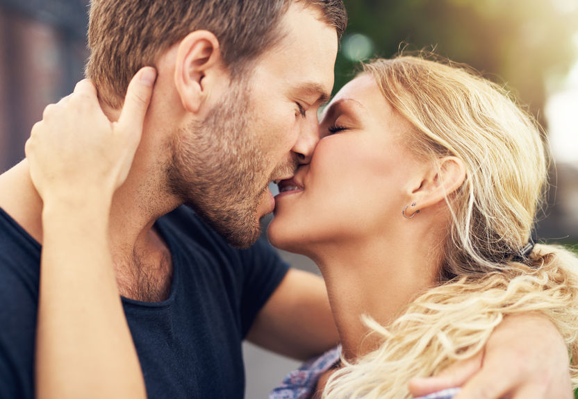 45029843 - young couple deeply in love sharing a romantic kiss, closeup profile view of their faces