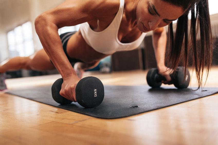 46946909 - muscular woman doing push-ups on dumbbells in gym. powerful female exercising in health club.