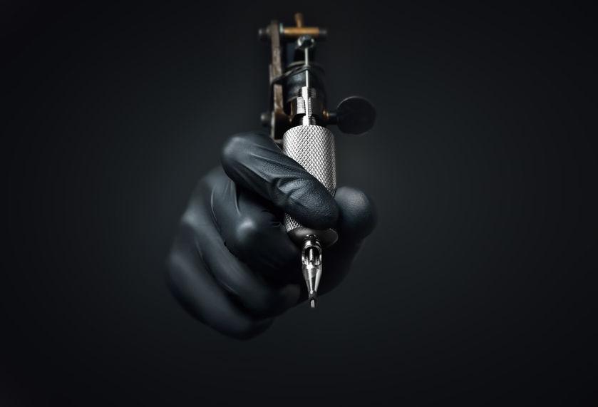 47256008 - tattoo artist holding tattoo machine on dark background, machine for a tattoo concept
