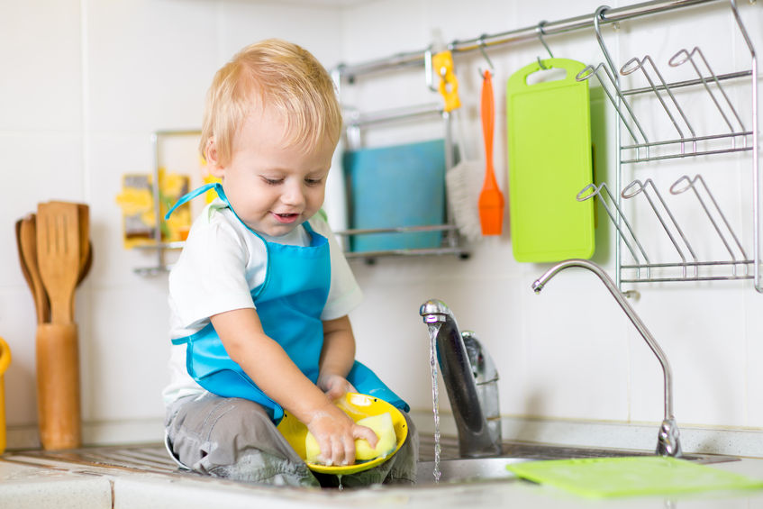 47999452 - cute child boy 2 years old washing up in kitchen