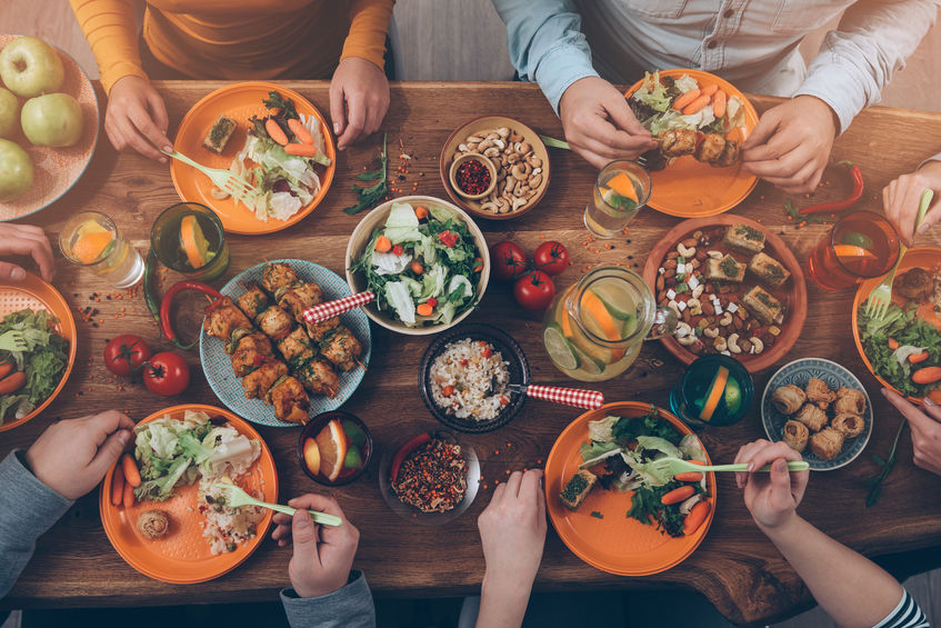 49263818 - enjoying dinner with friends. top view of group of people having dinner together while sitting at the rustic wooden table