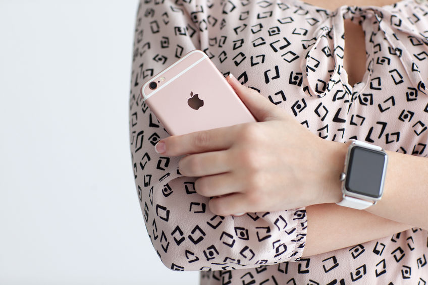 49316505 - alushta, russia - october 22, 2015: woman with apple watch in the hand holding iphone 6 s rose gold. iphone 6s and watch was created and developed by the apple inc.