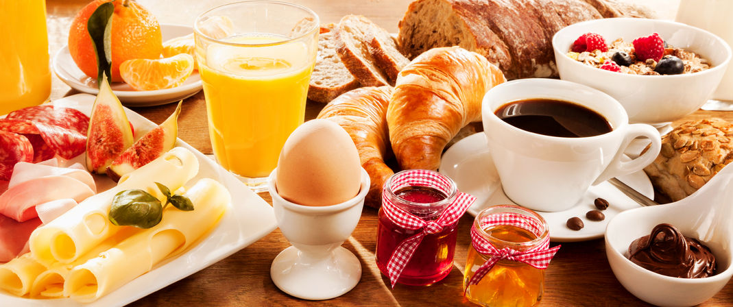 51721166 - breakfast feast with egg, meat, bread, coffee and juice